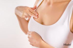 Woman performing breast exam