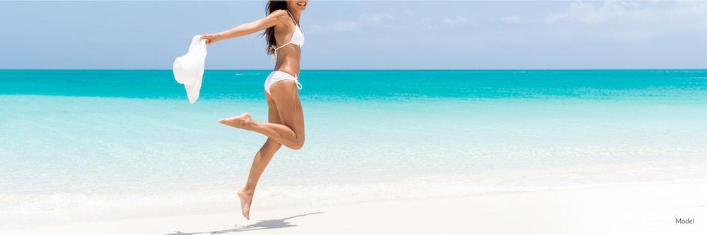 Happy woman dancing on beach in a bikini.